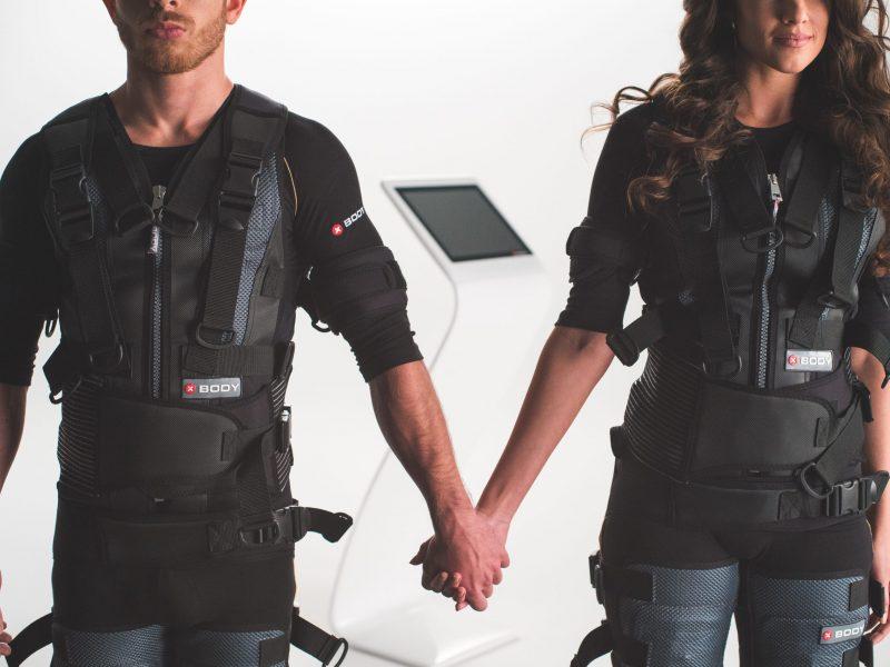 photo-couple-duo-homme-femme-qui-ce-tiens-la-main-en-combinaison-Xbody-avec-machine-Xbody-en-arriere-plans